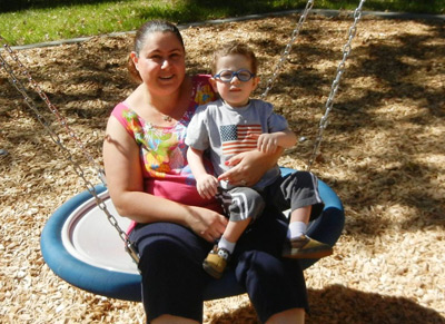 Mom holding young boy with glasses on swing