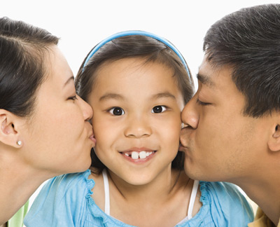 girl being kissed by her mom and dad