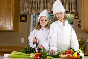 2 girls drwwed up as chefs in the kitchen preparing vegetables