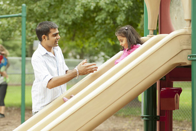 father helping daughter down a slide