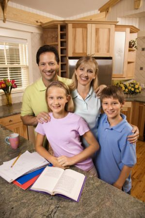 mother and father with son and daughter in the kitchen doing homework
